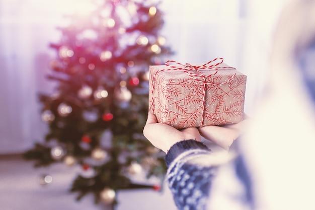 Les mains de la femme tiennent la boîte de cadeau de noël. joyeux noël