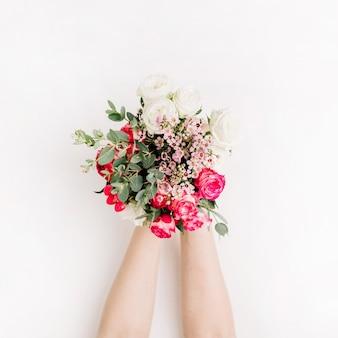 Les mains de la femme tiennent un bouquet de roses, une branche d'eucalyptus, des fleurs sauvages. mise à plat, vue de dessus