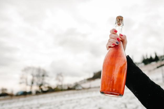 Les mains de la femme tiennent une bouteille de champagne contre les montagnes d'hiver.