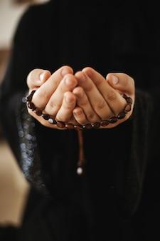 Les mains de la femme tiennent le chapelet pendant la prière