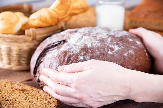 Les mains de la femme tiennent du pain fait maison traditionnel sombre sur une table en bois foncé