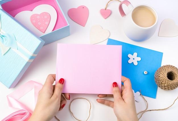 Les mains d'une femme tiennent une enveloppe rose sur un fond romantique dans des couleurs roses et bleues.