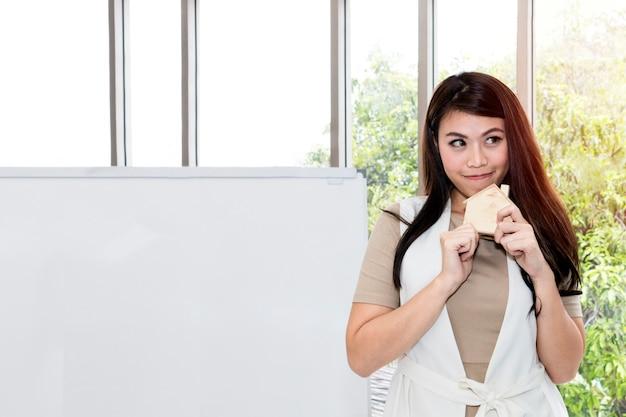 Des mains de femme tiennent le modèle de la maison en bois blanc.