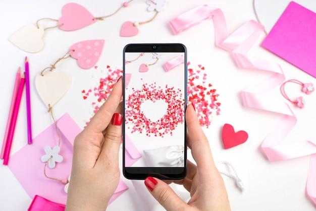 Les mains d'une femme tiennent le téléphone sur un fond romantique.