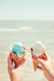 Les mains de la femme tient deux glaces sur la mer
