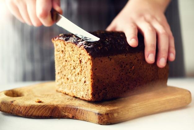 Mains de femme trancher du pain fraîchement sauvegardé.
