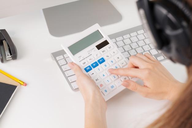Mains de femme travaillant avec calculatrice se bouchent