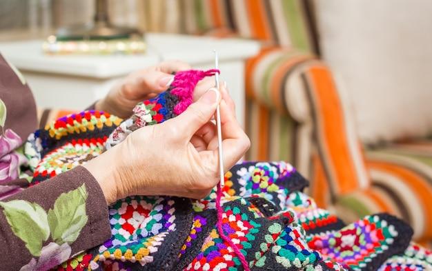 Mains de femme tricotant une courtepointe en laine vintage