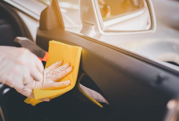 Mains de femme utilisant un chiffon de nettoyage en voituresécurité et protection contre l'infection pendant la pandémie du virus covid19