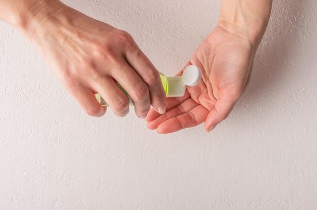 Mains de femme utilisant un gel désinfectant avec un désinfectant à base d'alcool liquide pour la prévention du coronavirus