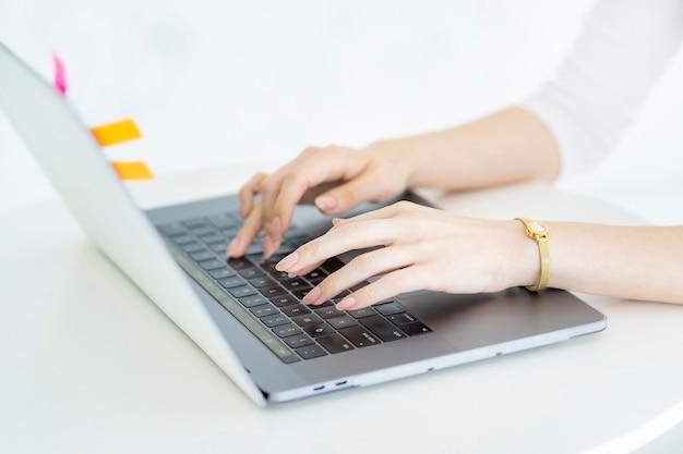 Mains d'une femme utilisant un ordinateur portable dans une pièce lumineuse