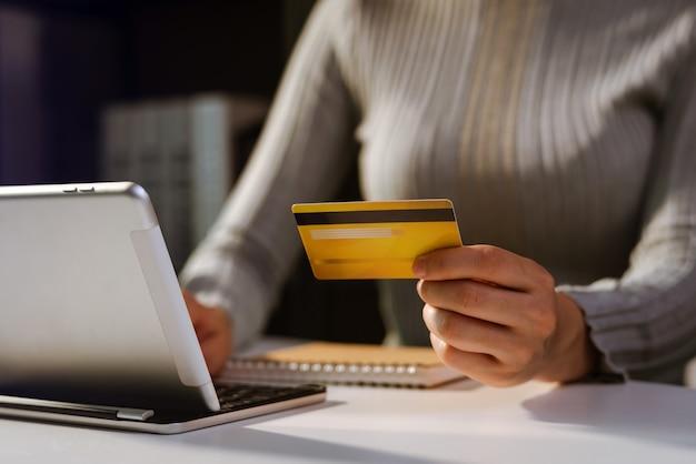 Mains de femme utilisant un smartphone et tenant une carte de crédit avec un diagramme d'effet de couche numérique comme concept d'achat en ligne