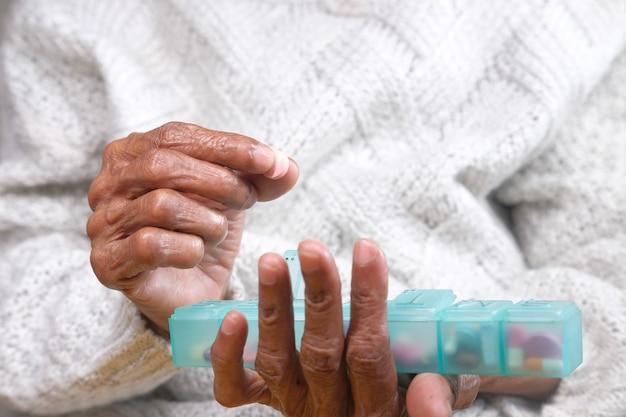 Mains de femmes âgées prenant des médicaments à partir d'une boîte à pilules