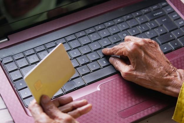 Mains de femmes âgées tenant une carte de crédit et utilisant un ordinateur portable pour acheter en ligne