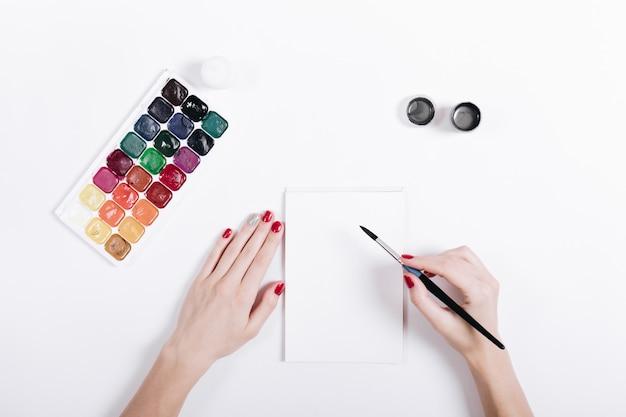 Mains de femmes avec des aquarelles peintes de vernis à ongles rouge dans un cahier