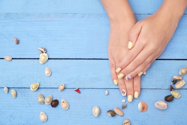 Mains de femmes avec une belle manucure et coquillages
