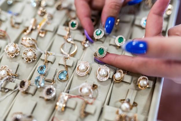 Les mains des femmes avec des bijoux en or se bouchent