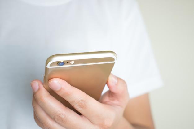 Les mains de femmes en chemise blanche regardent les médias sociaux au téléphone.