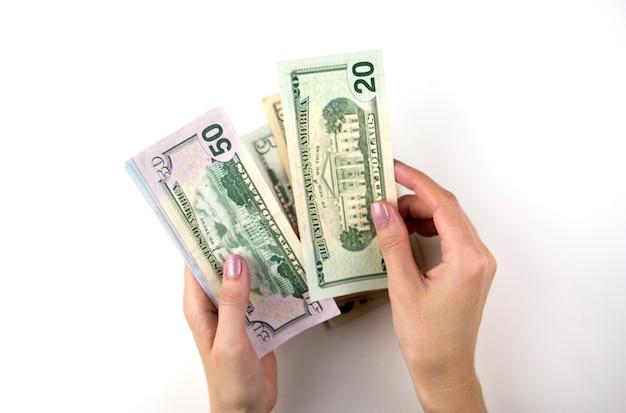 Les mains des femmes comptent de l'argent. la main de la femme recompte le paquet de dollars.