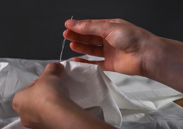 Mains de femmes de concept de couture manuelle avec l'aiguille et le tissu de coton la nuit