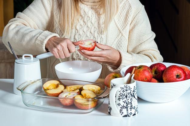 Les mains des femmes coupent une pomme et la préparent pour la cuisson, sur la table dans un bol blanc avec des pommes, concept de cuisson maison pour les vacances