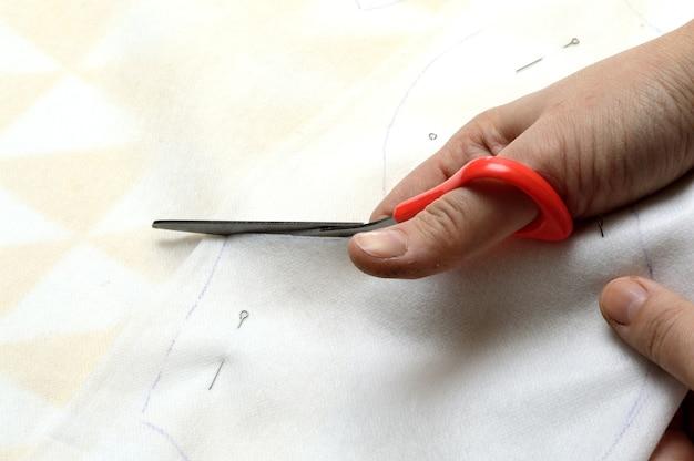 Les mains des femmes coupent le tissu avec des ciseaux selon le motif sur la table.