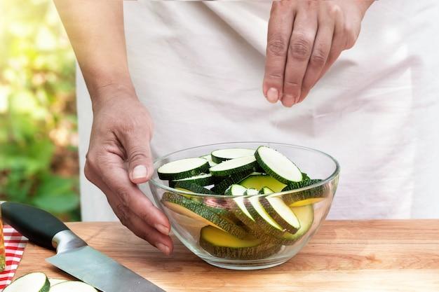 Les mains des femmes courgettes en tranches de sel dans un bol en verre