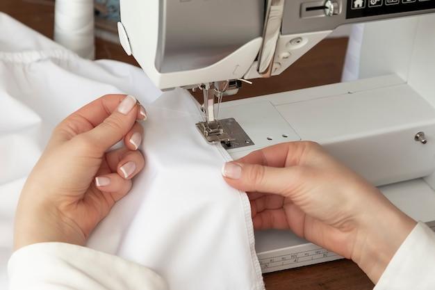 Les mains des femmes cousent du tissu blanc sur une machine de fabrication professionnelle sur le lieu de travail
