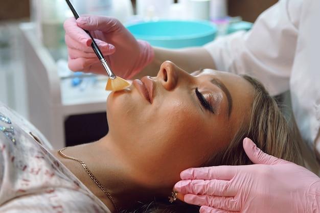 Les mains des femmes dans des gants roses font des procédures cosmétiques pour une patiente