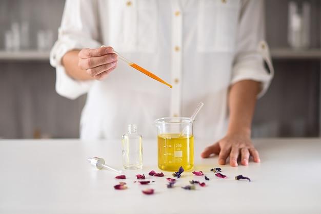 Les mains des femmes dans le laboratoire faisant du sérum