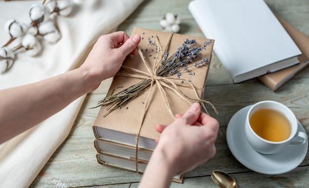 Les mains des femmes décorent soigneusement une pile de livres avec des couvertures en papier kraft avec de la corde et des fleurs de lavande