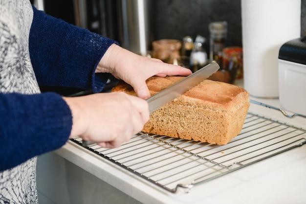Les mains des femmes avec du pain frais coupé au couteau
