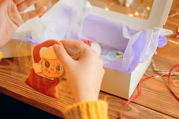 Les mains des femmes emballent du pain d'épice en forme de cochon dans des biscuits au chapeau du père noël avec un glaçage coloré dans une boîte sur...