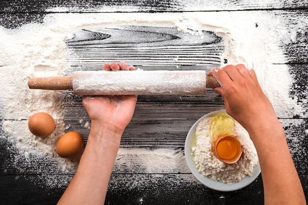 Les mains des femmes étalent la pâte sur une table noire saupoudrée de farine.