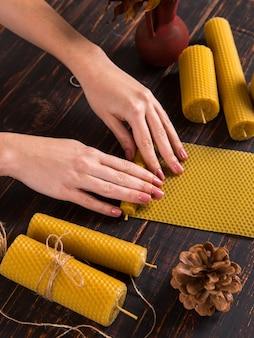 Les mains des femmes fabriquent des bougies artisanales en cire naturelle avec texture d'abeilles en nid d'abeille, sur une table en bois.
