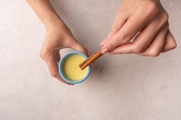 Les mains des femmes en forme de coeur tiennent une tasse en céramique bleue avec du thé chai masala indien traditionnel