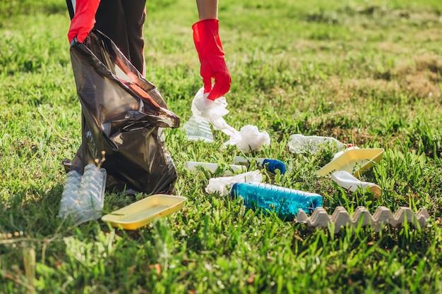 Mains de femmes en gants de caoutchouc rouge. la femme recueille les ordures dans le sac. des bénévoles récupèrent les ordures dans le parc d'été. belle femme progressiste faisant un effort pour aider l'environnement
