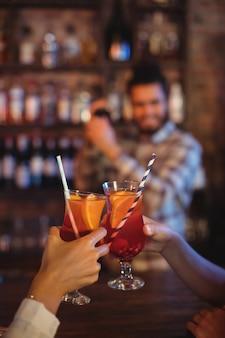 Mains de femmes grillant leurs cocktails au comptoir