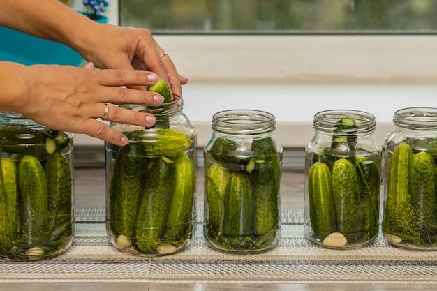 Les mains des femmes lors de la préparation des concombres en conserve dans des bocaux en verre.