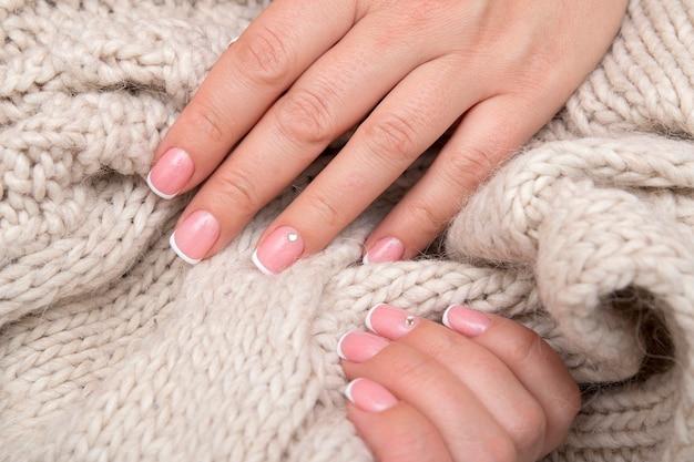 Mains de femmes avec manucure française et strass sur des ongles rectangulaires sur le fond d'un pull. concept d'hiver