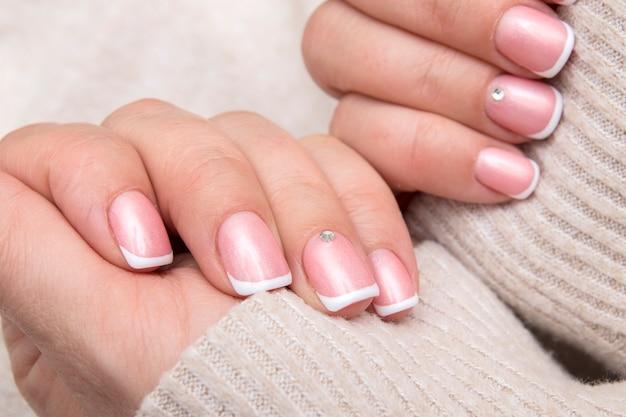 Mains de femmes avec manucure française et strass sur des ongles rectangulaires sur le fond d'un pull