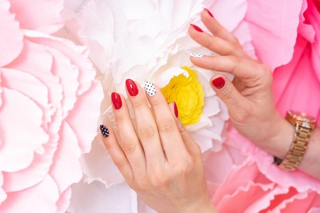 Les mains des femmes. manucure multicolore utilisant des couleurs rouge, noir, blanc.