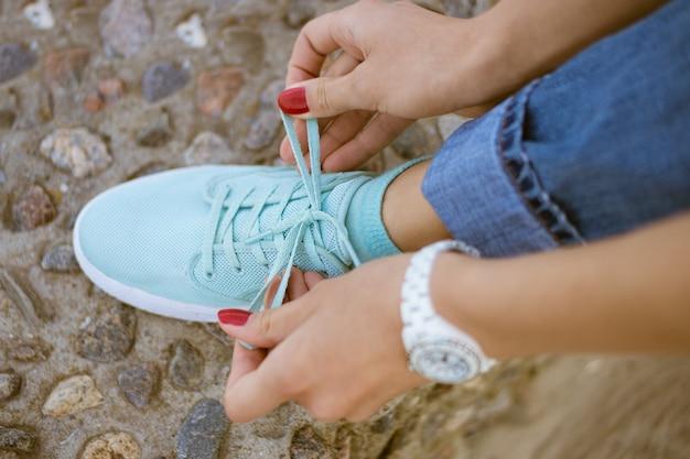 Mains de femmes avec une manucure rouge lacets noués sur des chaussures de sport