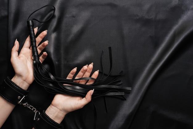 Les mains des femmes menottes aux poignets sur une feuille de soie sombre avec un fouet