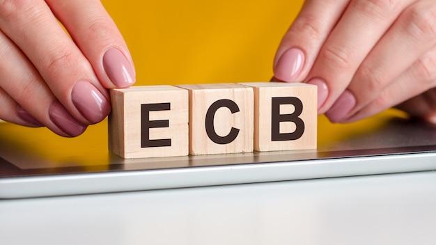 Les mains des femmes met un bloc de bois avec les lettres ecb sur la surface noire du bloc-notes ecb court pour entreprise à gouvernement concept d'entreprise surface jaune mise au point sélective