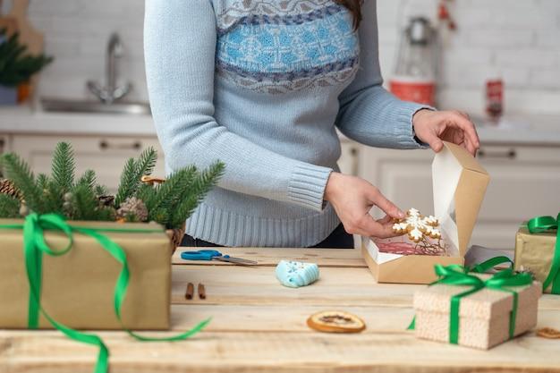 Les mains des femmes mettent des biscuits dans une boîte