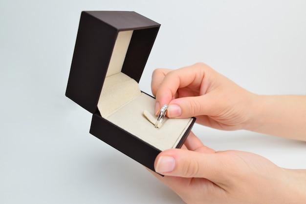 Les mains des femmes ouvrent une boîte avec une bague en diamant sur fond blanc