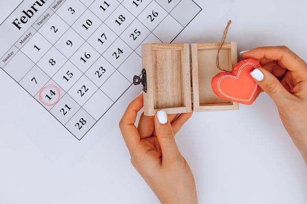 Les mains des femmes ouvrent un cadeau avec un cœur à l'intérieur sur blanc