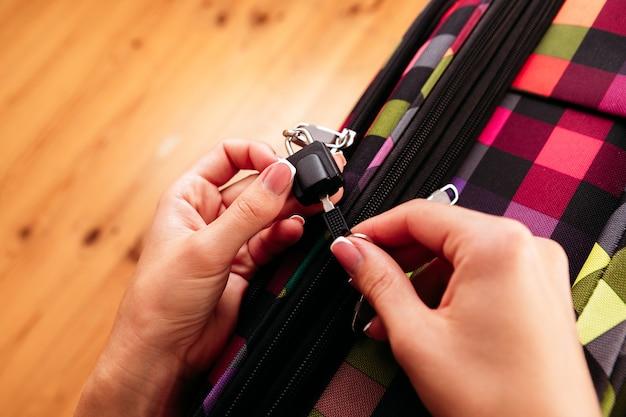 Les mains des femmes ouvrent une valise avec des choses. concept de voyage