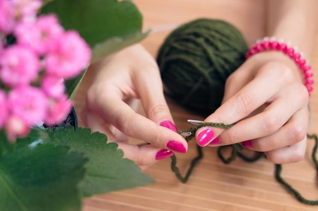 Mains de femmes avec rayons en métal tricoté manucure rose